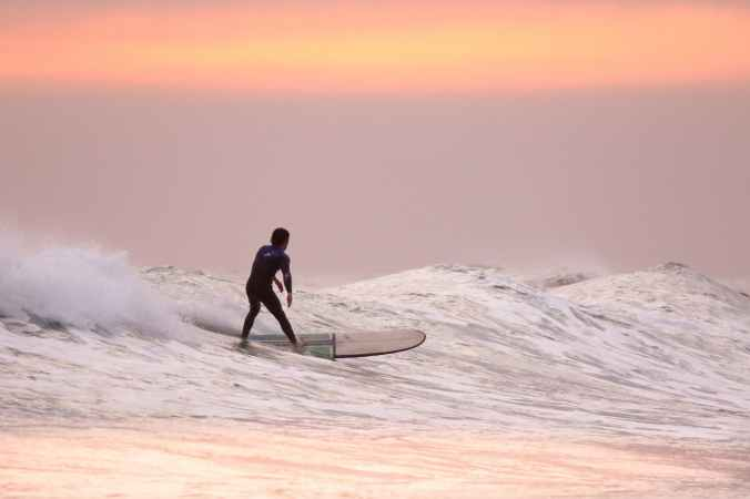 person surfing with an orange and pink sky behind them